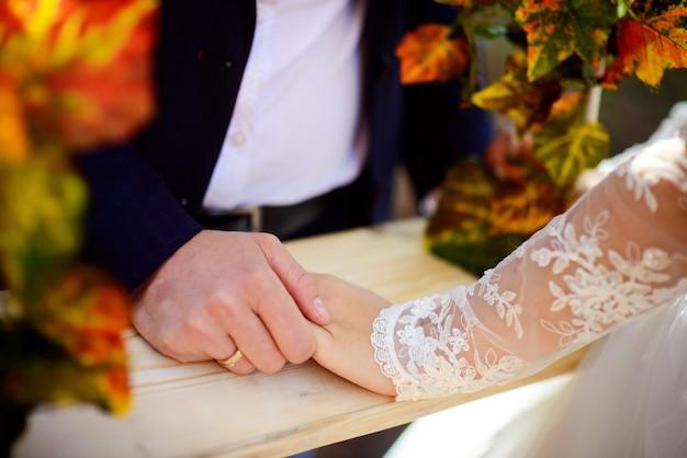 La mano degli sposi con l'anello dorato tiene la mano della sposa sulla superficie di legno.