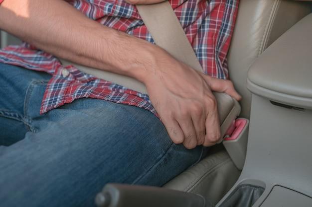 La mano degli uomini allaccia la cintura di sicurezza dell'auto
