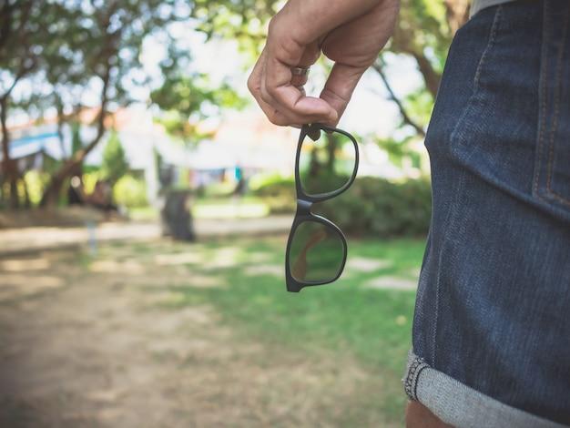 La mano degli uomini dei pantaloni a vita bassa tiene gli occhiali mentre viaggiava nel parco naturale