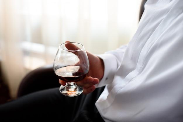 La mano degli uomini tiene un bicchiere di cognac.