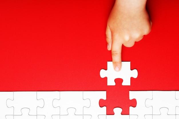 La mano dei bambini muove un pezzo di puzzle bianco su uno sfondo rosso