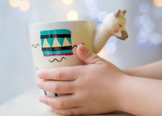 La mano dei bambini tiene la tazza con una tazza alla moda a forma di lama con una bevanda calda con luci