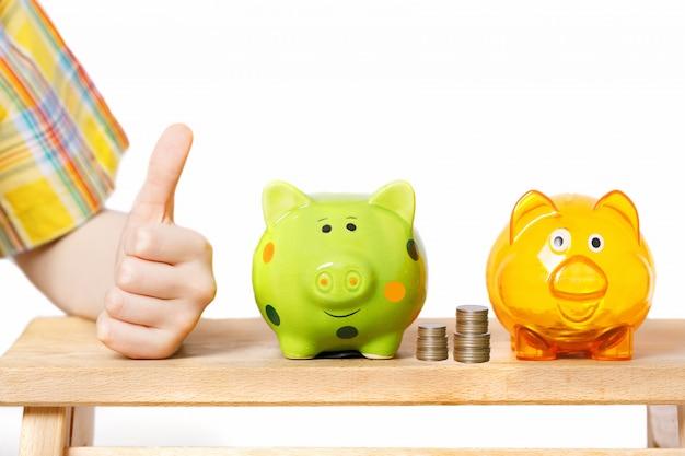La mano del bambino che mostra i pollici aumenta e monete vicino ad un porcellino salvadanaio.