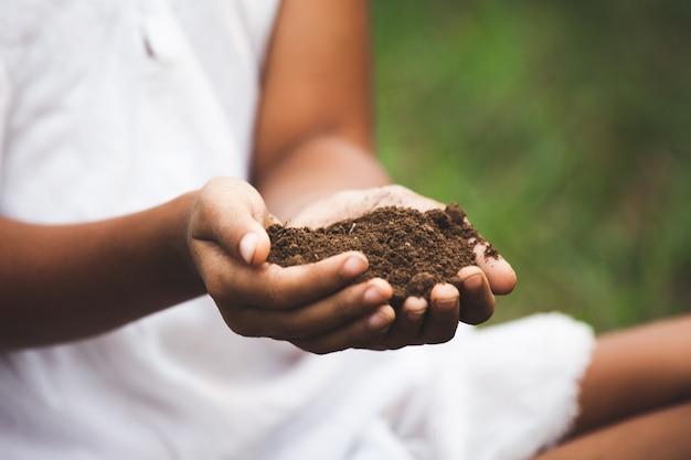 La mano del bambino che tiene il terreno prepara per piantare l'albero