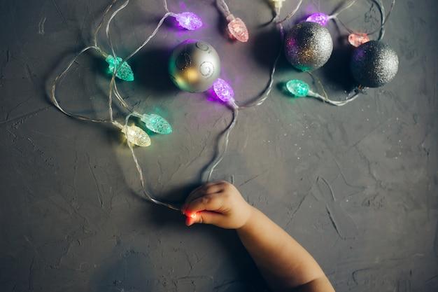La mano del bambino che tiene la ghirlanda leggera, le bagattelle, la decorazione di natale