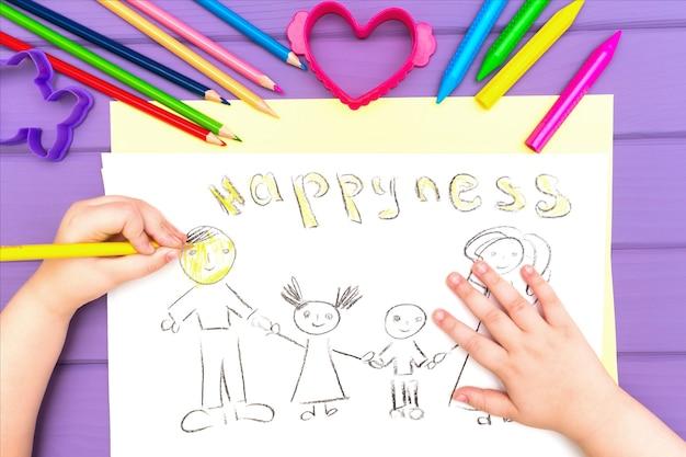La mano del bambino dipinge lo schizzo della famiglia