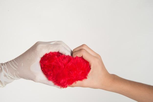 La mano del bambino e del medico si toccano con il cuore in mano