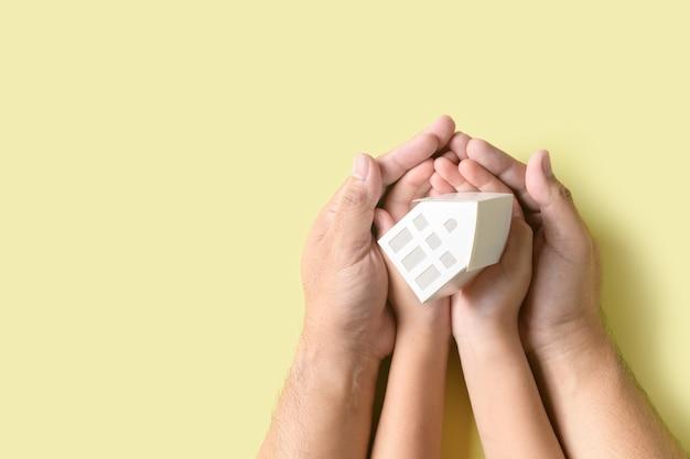 La mano del bambino e del padre che tiene la piccola casa di modello in mani