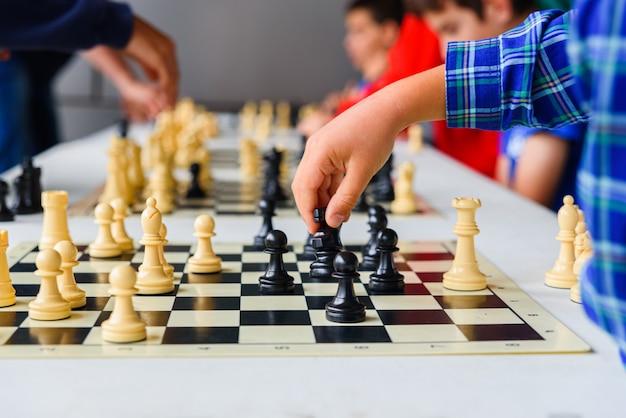 La mano del bambino muove il cavallo durante un torneo di scacchi con diverse schede di gioco.