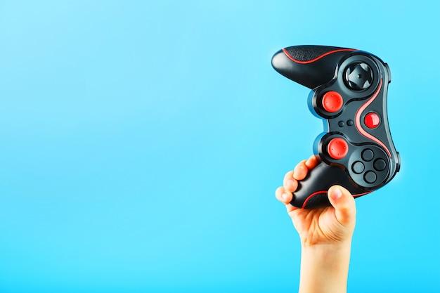 La mano del bambino tiene trionfalmente il gamepad su una superficie blu