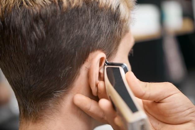 La mano del barbiere usando la tosatrice, facendo un nuovo taglio di capelli per il cliente.