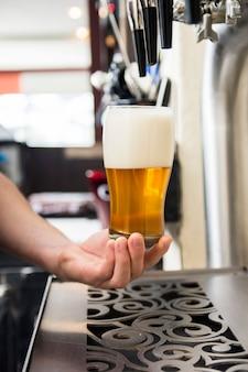 La mano del barista che tiene un grande bicchiere di birra sotto l'etichetta