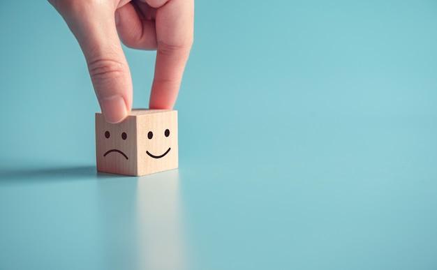 La mano del cliente da vicino sceglie la faccina sorridente e l'icona della faccia triste sul cubo di legno