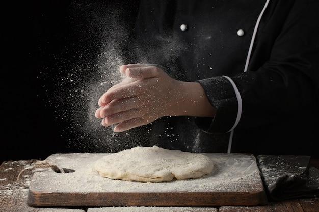 La mano del cuoco unico della donna applaude con spruzzata di farina bianca.