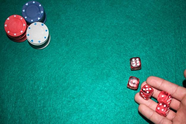La mano del giocatore di poker che lancia i dadi rossi sul tavolo da poker