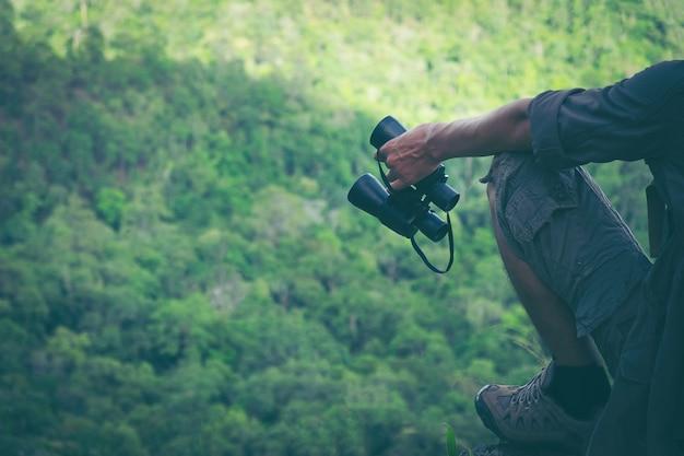 La mano del giovane sta tenendo un binocolo con lo zaino che si rilassa sopra una montagna