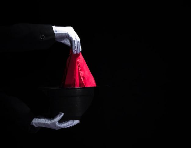 La mano del mago che esegue il trucco magico con il tovagliolo sopra il cappello nero superiore