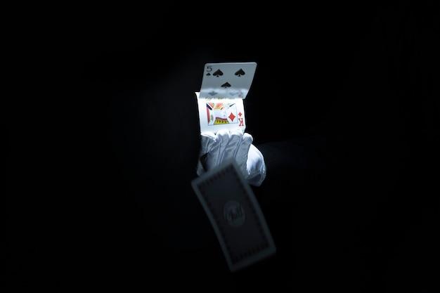 La mano del mago che getta le carte da gioco contro fondo nero