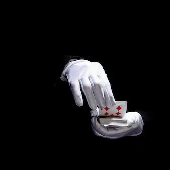 La mano del mago che indossa i guanti bianchi che tengono le carte da gioco contro fondo nero