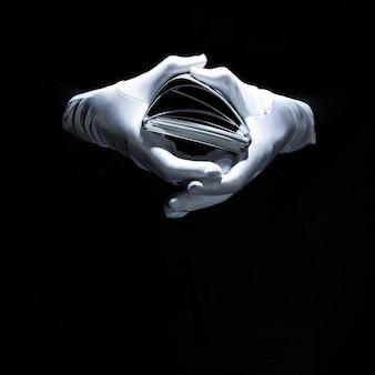 La mano del mago che indossa la pila bianca delle carte da gioco della tenuta del guanto