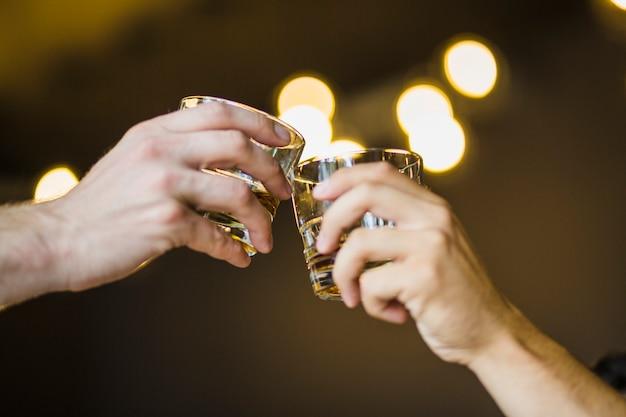 La mano del maschio che tosta il vetro delle bevande contro il fondo illuminato del bokeh