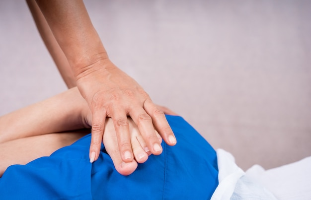 La mano del massaggiatore sta massaggiando una gamba della donna