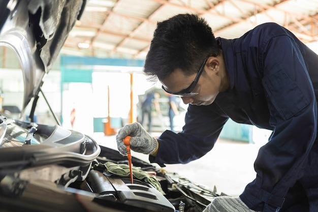 La mano del meccanico di automobili controlla l'olio motore per la manutenzione nell'auto di servizio del garage.