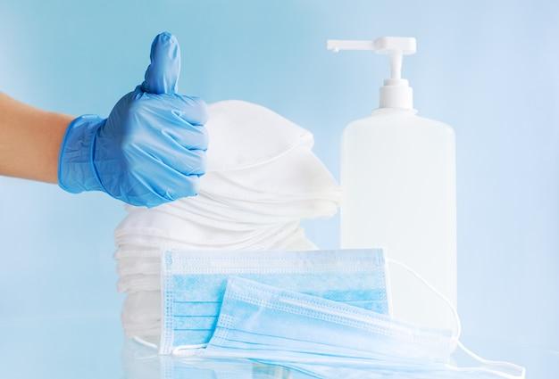 La mano del medico in guanti blu mostra i pollici aumenta il segno. molte diverse maschere mediche, maschera chirurgica monouso protettiva, gel disinfettante per alcol