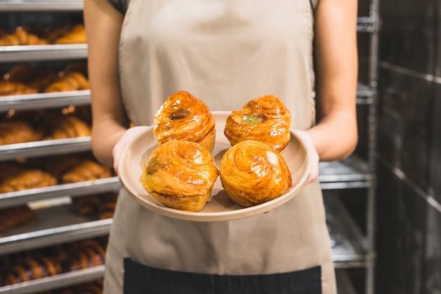 La mano del panettiere femminile che tiene pasta sfoglia dolce sul piatto