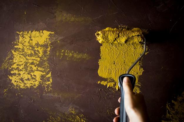 La mano del pittore di casa è dipinta di giallo sulla vecchia parete marrone con spazio di copia.