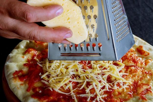 La mano del primo piano del panettiere del cuoco unico che produce la pizza al cuoco unico della cucina sfrega il formaggio
