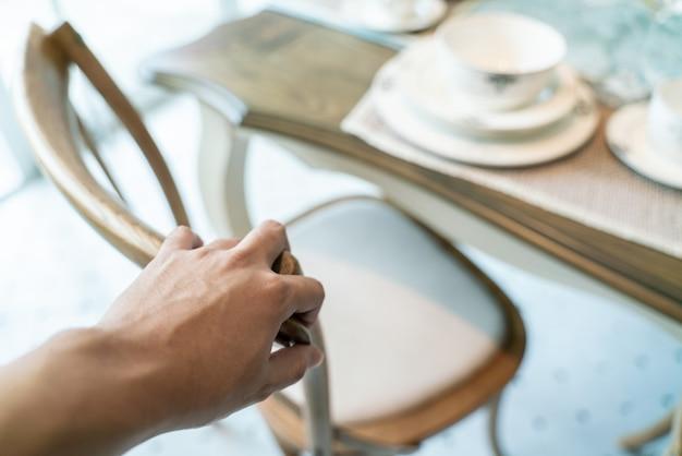 La mano del primo piano trascina una sedia per muoversi.