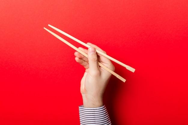 La mano del ragazzo che mostra le bacchette su colore rosso