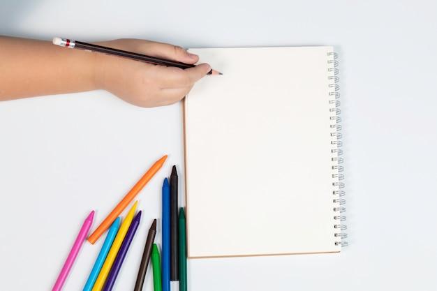 La mano del ragazzo di vista superiore tiene la matita con il modello del taccuino di carta