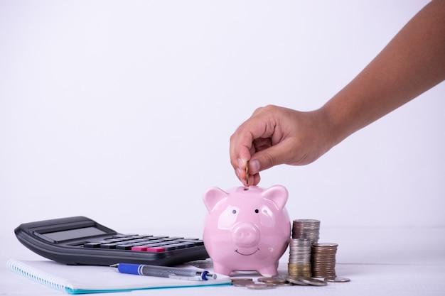 La mano del ragazzo ha messo le monete al porcellino salvadanaio, pila di monete, calcoli, concetto dei soldi di risparmio.