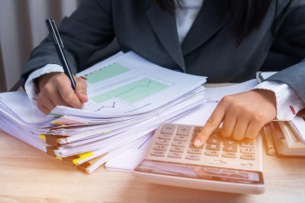La mano del ragioniere calcola il rapporto finanziario che conta il controllo dei dati finanziari che analizzano il documento