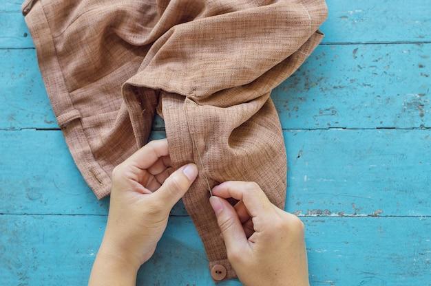 La mano del sarto ripara i pantaloni marroni
