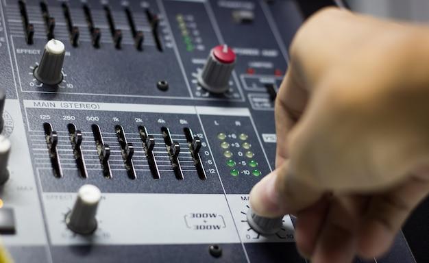 La mano del tecnico del suono regola l'interfaccia del miscelatore