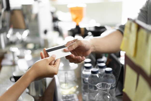 La mano dell'acquirente dà una carta di credito al venditore