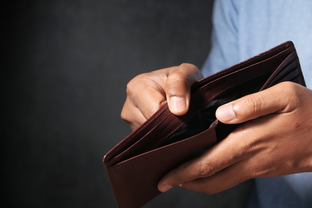 La mano dell'uomo apre un portafoglio vuoto con lo spazio della copia.