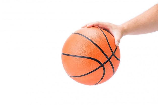 La mano dell'uomo asiatico sta giudicando o palming una pallacanestro arancio a disposizione isolata
