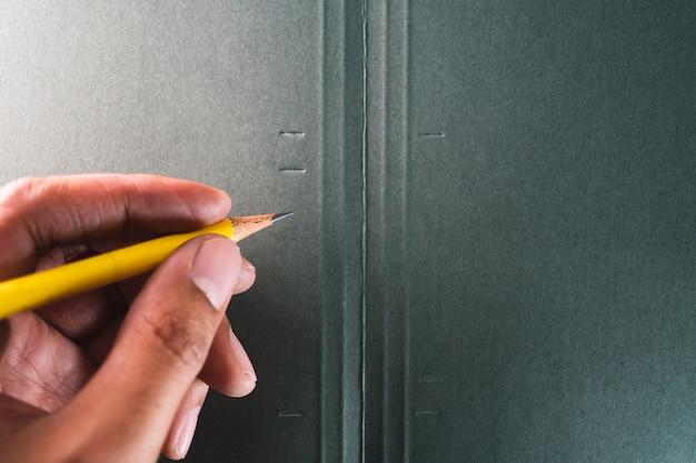 La mano dell'uomo asiatico tiene una matita gialla su carta verde scuro