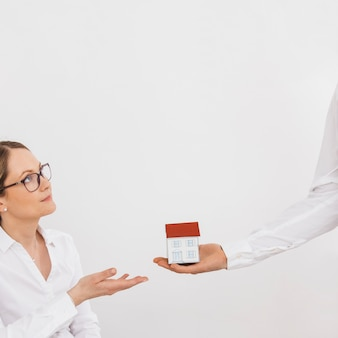 La mano dell'uomo che dà il modello di casa in miniatura alla giovane donna contro il muro bianco