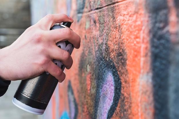 La mano dell'uomo che disegna i graffiti sulla parete con la latta dell'aerosol