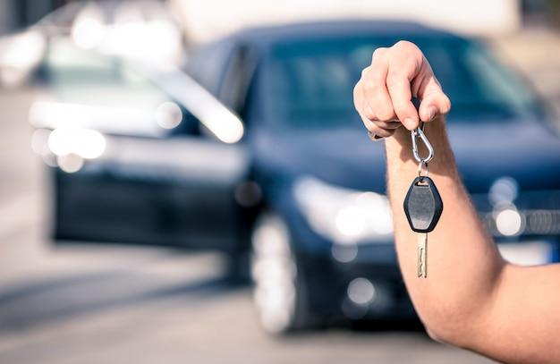 La mano dell'uomo che giudica le chiavi moderne dell'automobile pronte per il noleggio