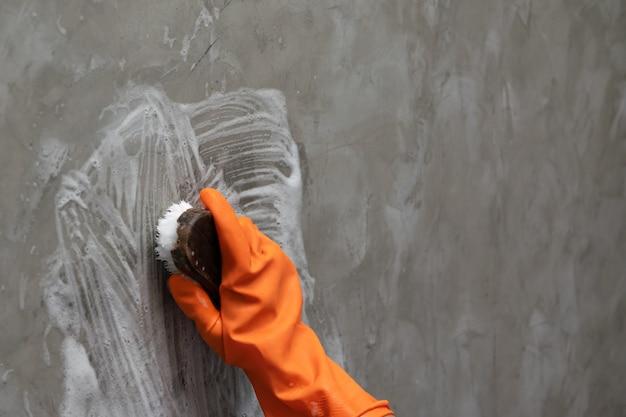 La mano dell'uomo che indossa guanti di gomma arancione viene utilizzata per convertire la pulizia della macchia sul cemento