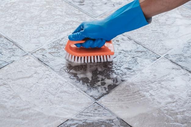 La mano dell'uomo che indossa guanti di gomma blu viene utilizzata per convertire la pulizia dello scrub sul pavimento piastrellato.