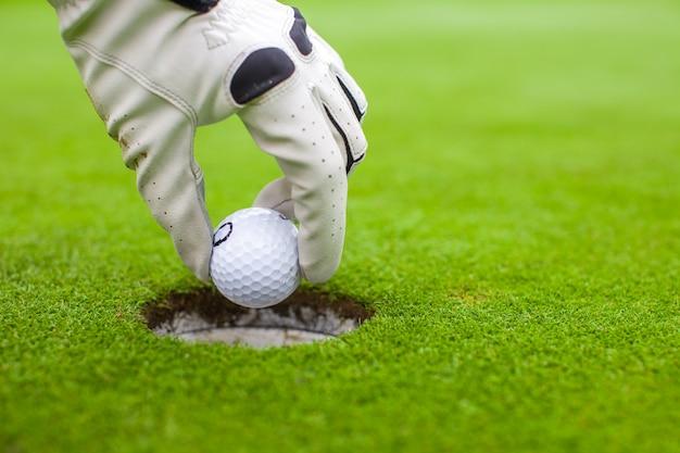 La mano dell'uomo che mette una pallina da golf nel foro sul campo verde