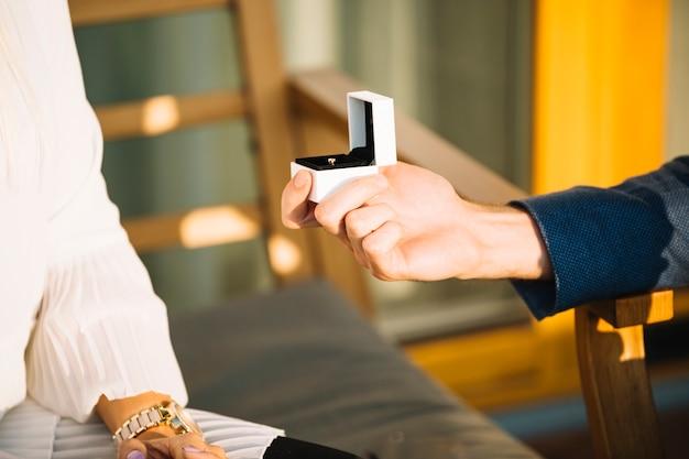 La mano dell'uomo che mostra la scatola dell'anello di fidanzamento alla sua ragazza