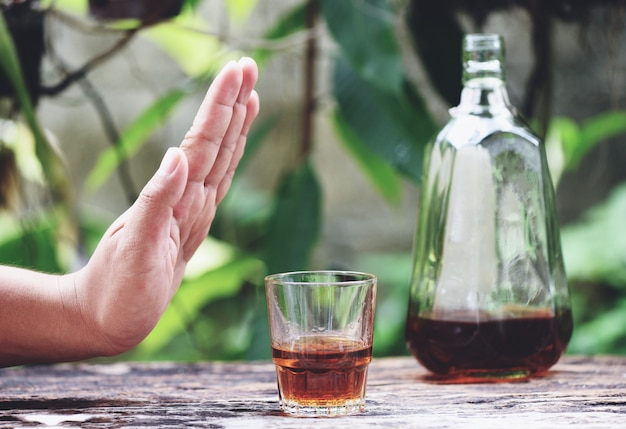 La mano dell'uomo che rifiuta il vetro con la bevanda alcolica sulla superficie della tavola all'aperto rifiuta di bere un whisky dell'alcool